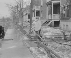 homme arrosant son trottoir